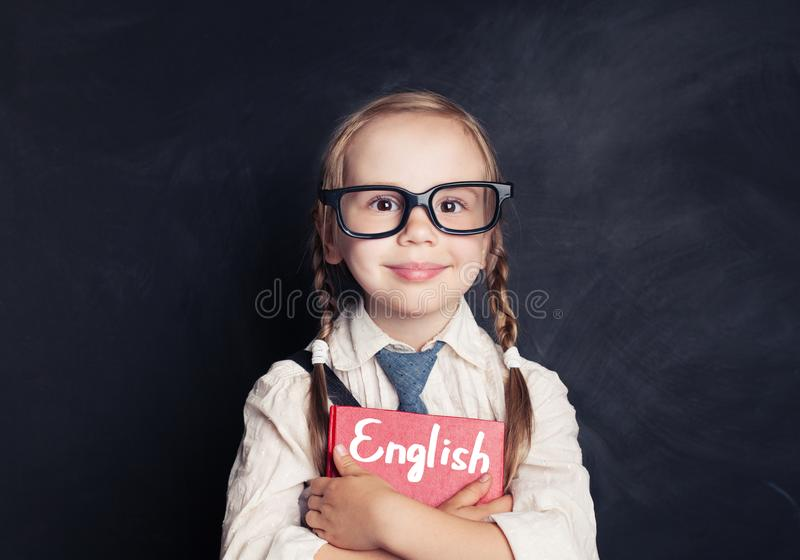 Colegiala linda del niño que sostiene el libro rojo en la pizarra imágenes de archivo libres de regalías