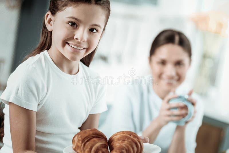 Colegiala linda que come los cruasanes sabrosos en la cocina imagenes de archivo