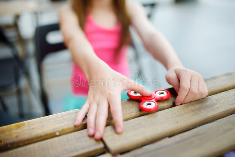 Colegiala linda que juega con el hilandero colorido de la persona agitada fotos de archivo