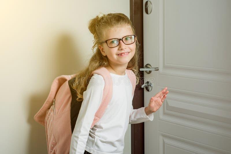 Colegiala menor linda con el pelo rubio que va a la escuela, colocándose fotografía de archivo