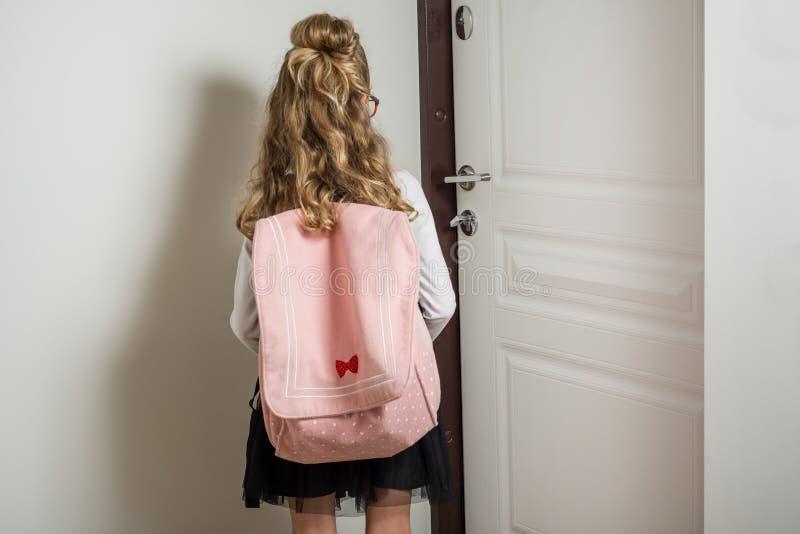 Colegiala menor linda con el pelo rubio que va a la escuela, colocándose fotografía de archivo libre de regalías
