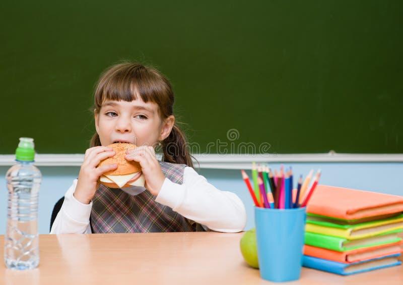 Colegiala que come los alimentos de preparación rápida mientras que almorzando imagen de archivo