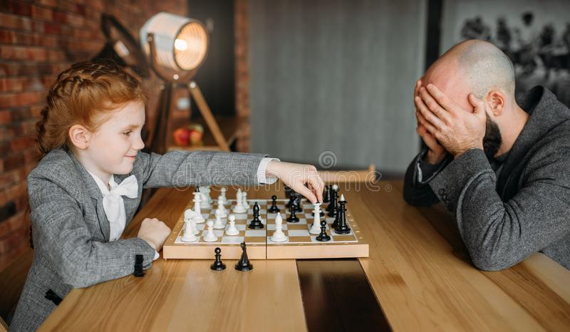 Colegiala que juega a ajedrez con la persona masculina adulta fotografía de archivo libre de regalías