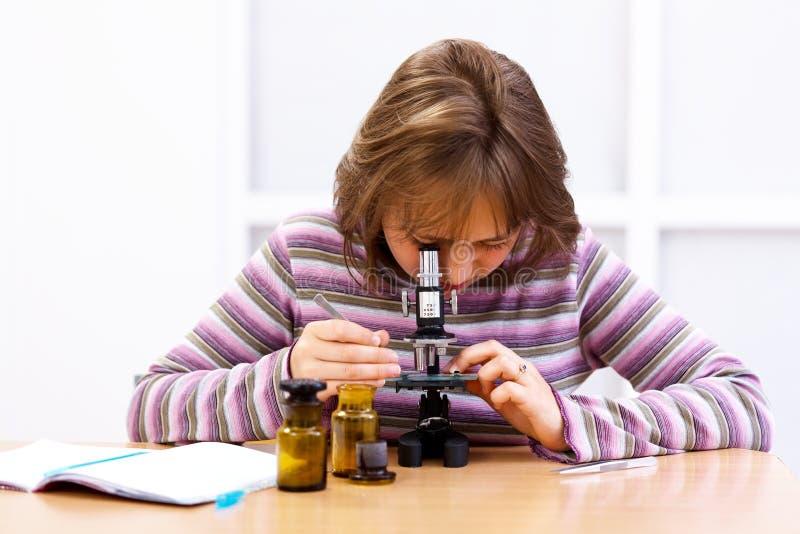 Colegiala que mira en el microscopio foto de archivo libre de regalías