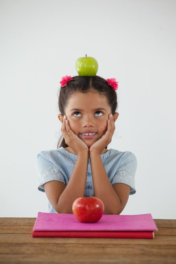 Colegiala que se sienta con la manzana verde en su cabeza contra el fondo blanco imagen de archivo libre de regalías