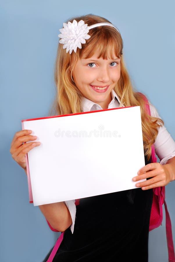 Colegiala que sostiene la tarjeta en blanco imágenes de archivo libres de regalías