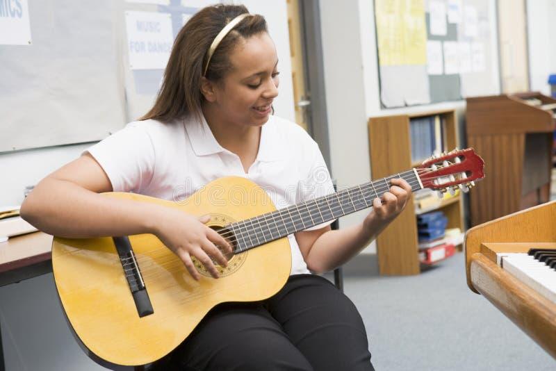 Colegiala que toca la guitarra en clase de música foto de archivo libre de regalías