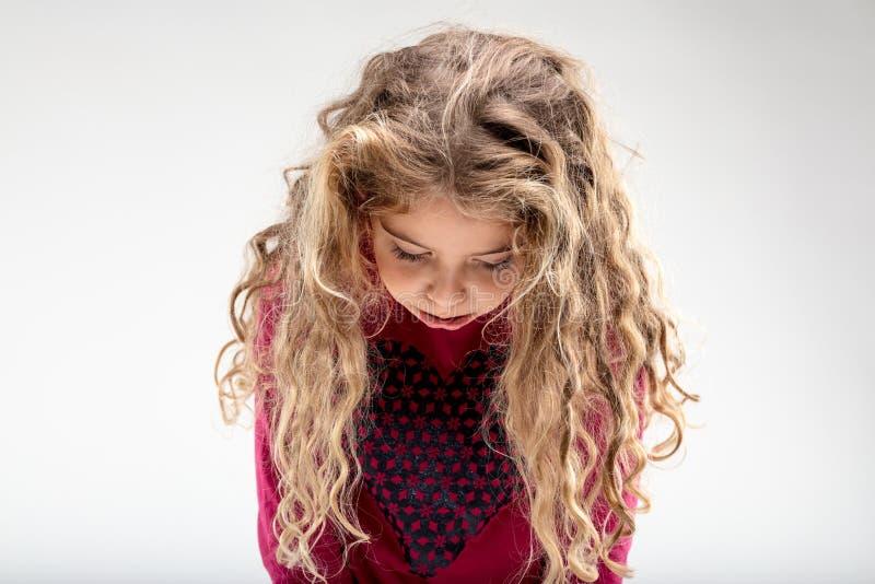 Colegiala rizado-cabelluda triste con la cabeza abajo foto de archivo