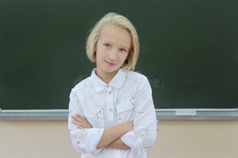 Colegiala rubia adorable 9-11 años en una sala de clase cerca de una pizarra De nuevo a escuela fotos de archivo libres de regalías