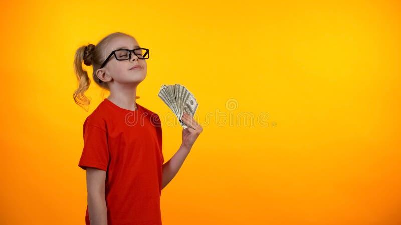 Colegiala sonriente en los vidrios que sostienen el manojo de billetes de banco del dólar, primera renta imagenes de archivo