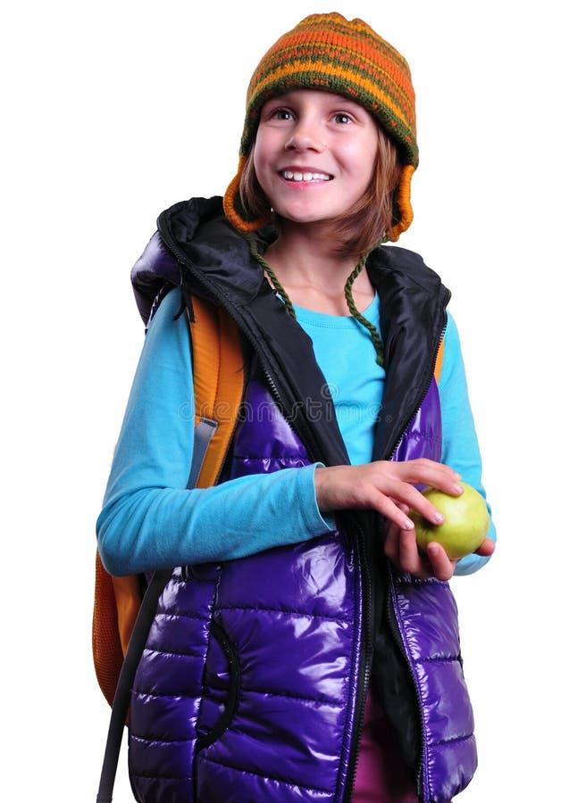 Colegiala sonriente feliz con la mochila y manzana aislada sobre blanco imagen de archivo libre de regalías