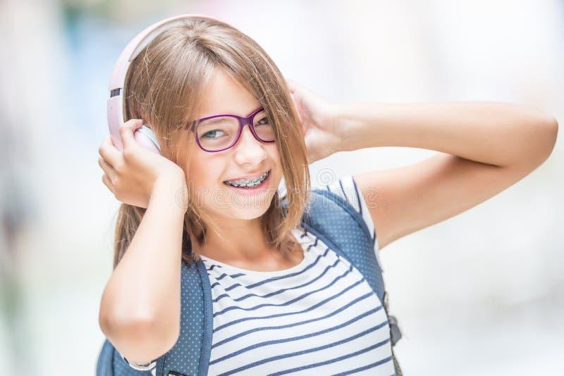 Colegiala sonriente feliz con los apoyos dentales y m?sica que escucha de los vidrios de los auriculares Concepto del Orthodontis fotografía de archivo