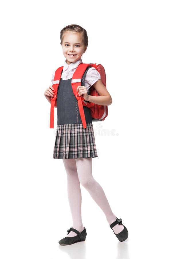 Colegiala sonriente linda en el uniforme que se coloca encendido fotografía de archivo libre de regalías