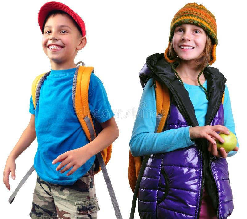 Colegiala y muchacho sonrientes felices con las mochilas aisladas fotos de archivo