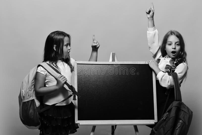 Colegialas al lado de la pizarra en fondo rosado Las muchachas con las caras sorprendidas sostienen los fingeres para arriba que  imagen de archivo libre de regalías
