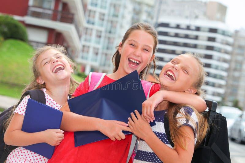 Colegialas felices con las mochilas fotografía de archivo