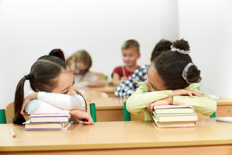 Colegialas que duermen en sala de clase en el escritorio, inclinándose en los libros foto de archivo libre de regalías