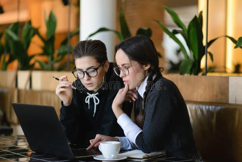 Colegialas que hacen la preparación usando el ordenador portátil fotografía de archivo