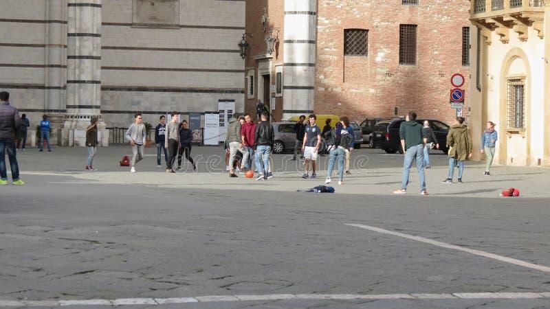 Colegiales y colegialas italianos en un schooltrip que juega el pie en el cuadrado de la catedral fotos de archivo