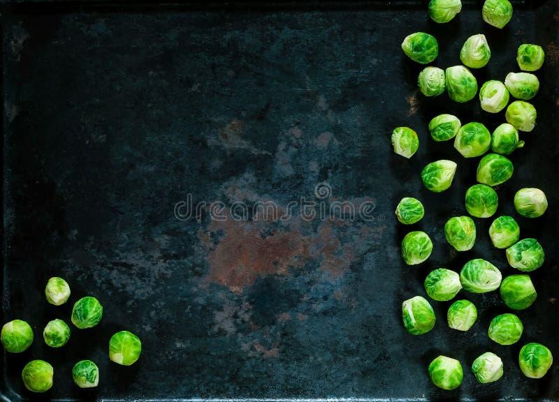 Coles de Bruselas frescas en fondo oxidado del metal del vintage, verduras para cocinar sano, endecha del plano, espacio de la co imagen de archivo