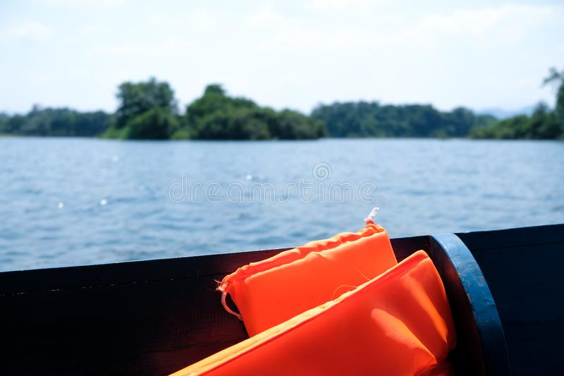 Colete salva-vidas laranja a bordo de um barco no meio do lago foto de stock