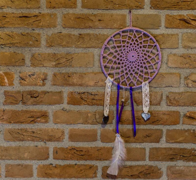 Coletor ideal feito à mão bonito que pendura em uma parede de tijolo, decorações da casa, fundo espiritual imagens de stock royalty free