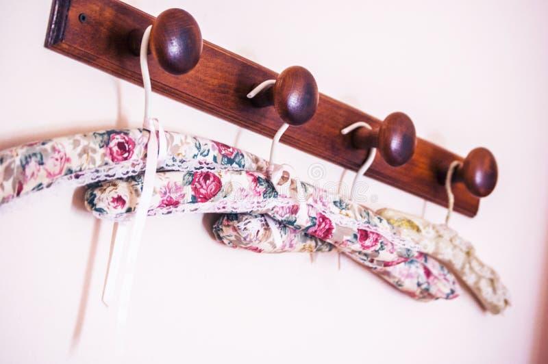 Colgador selectivo ropas con motivos florales colgadas en una barra de madera marrón imagenes de archivo
