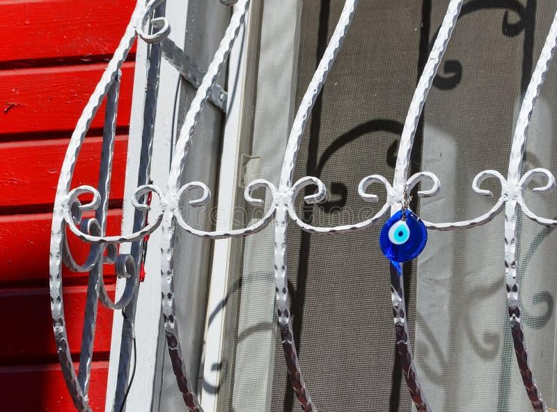 Colgante de cristal redondo azul bajo la forma de ojo que cuelga en una ventana del enrejado Amuleto turco tradicional - boncuk d imagen de archivo libre de regalías
