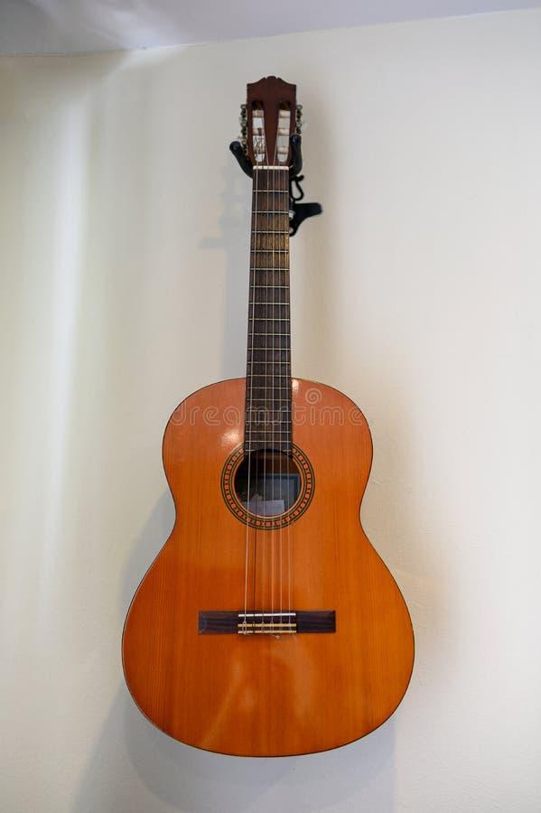 Colgante de la guitarra acústica decorativo en la pared imagenes de archivo