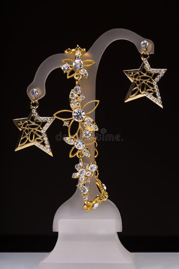 Colgante del oro y pendientes bajo la forma de estrellas ilustración del vector