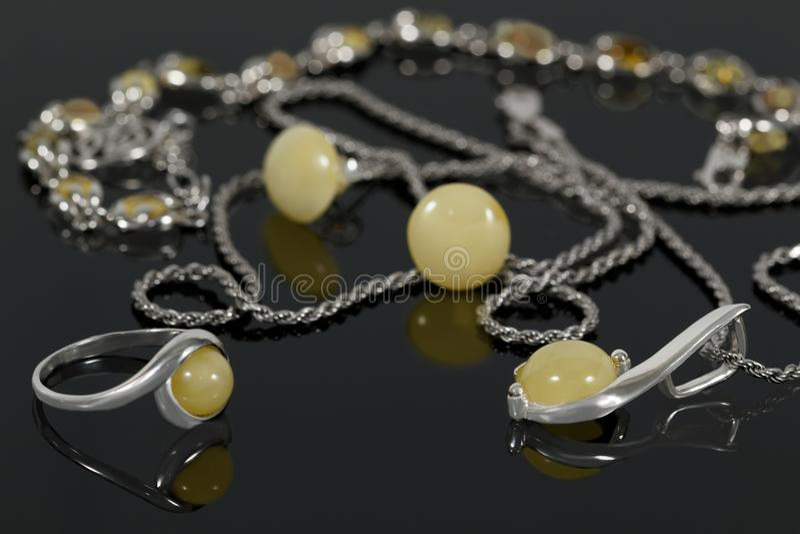 Colgante y anillo de plata del primer en los pendientes y la pulsera del fondo en el escritorio de acrílico negro imagenes de archivo