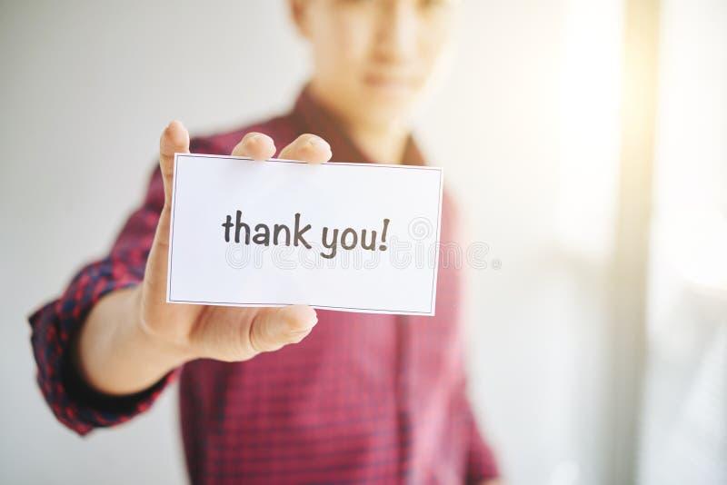 Colha o homem que guarda o cartão com agradecem-lhe palavras fotografia de stock royalty free