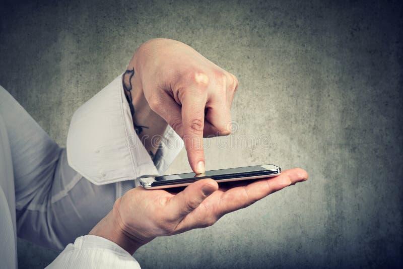 Colha o tiro de um dedo da mão do homem que bate no smartphone foto de stock