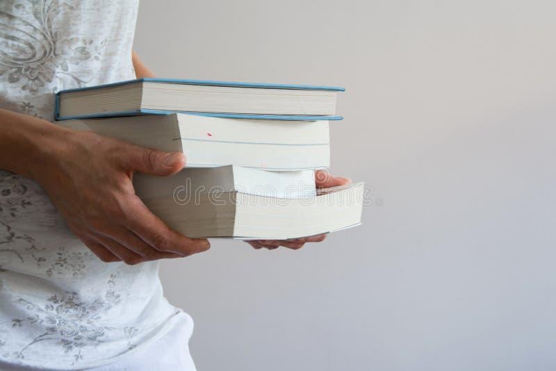 Colha a opinião a jovem mulher que guarda uma pilha dos livros imagem de stock