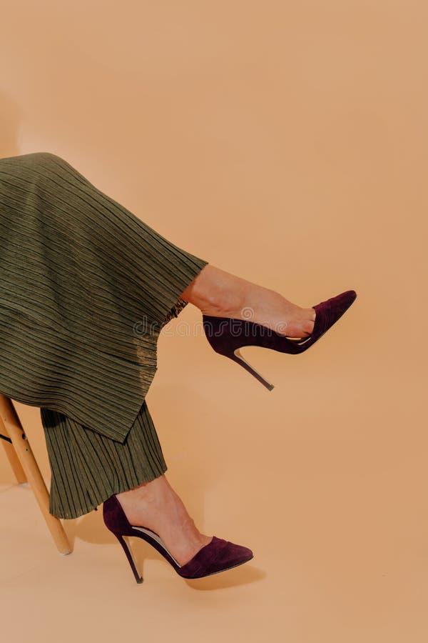 Colheita disparada dos pés da mulher bonita elegante nos saltos altos que sentam-se no fundo bege imagens de stock royalty free