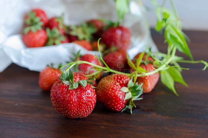 Colheita do verão de morangos saborosos maduras suculentas com o galho verde na tabela escura imagem de stock