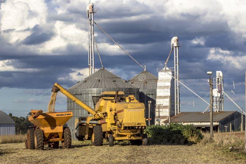 Colheita mecanizada do feijão de soja na frente do silo imagens de stock