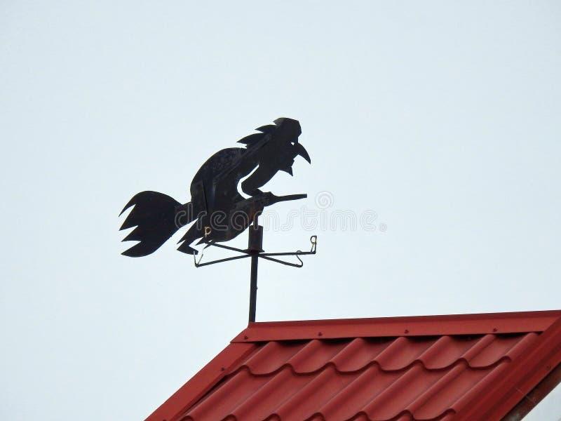 Colheita metálica preta da bruxa no telhado home, Lituânia fotos de stock