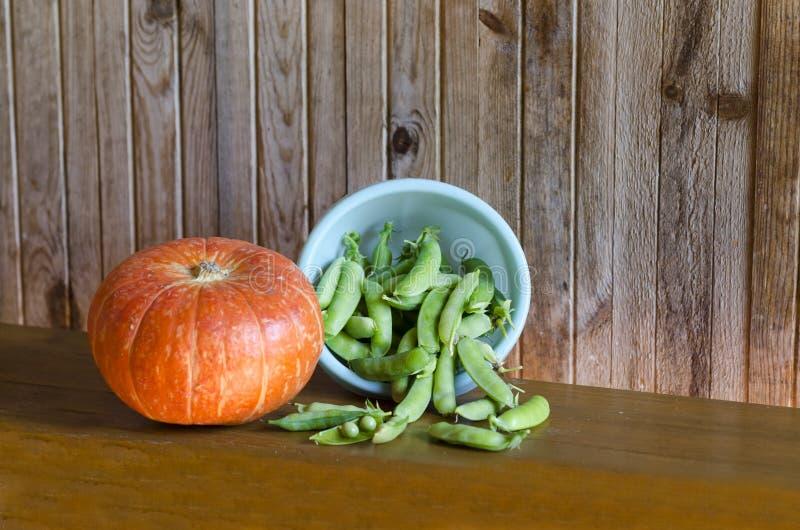Colheita nova fresca, abóbora alaranjada da colheita e ervilhas verdes novas em um fundo de madeira foco macio, espaço da cópia,  foto de stock