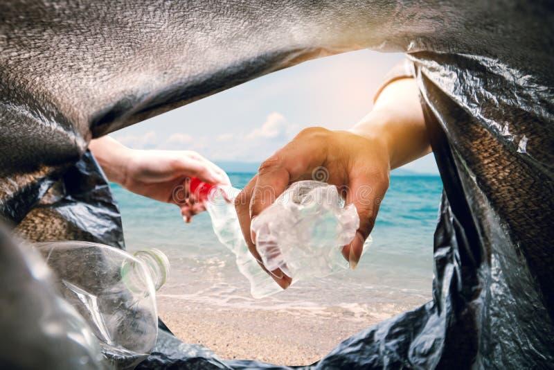 A colheita voluntária acima uma garrafa plástica dentro a um saco do escaninho e ao fundo do mar imagens de stock