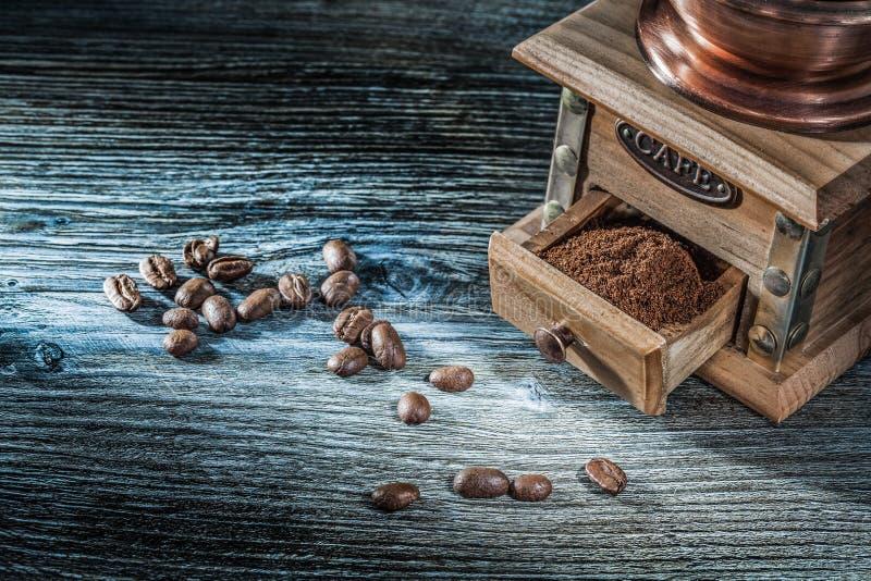 Colheitas do moedor de café na placa de madeira do vintage imagens de stock