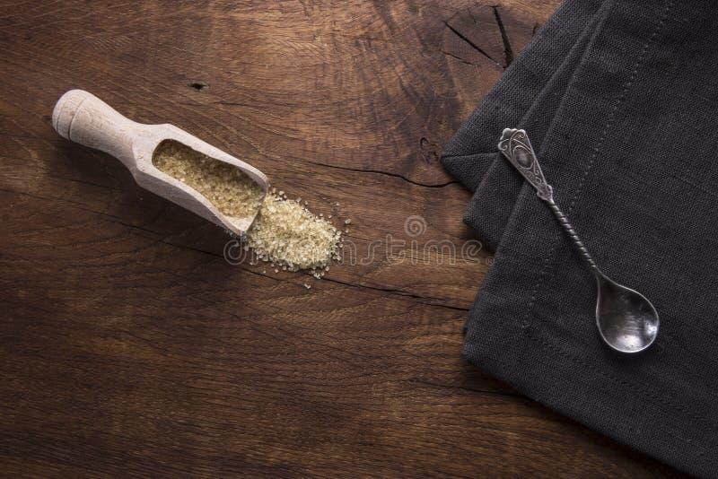 Colher com açúcar mascavado, no fundo de madeira velho imagens de stock royalty free