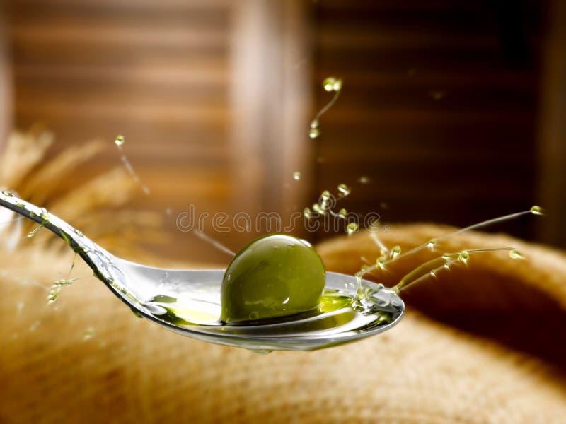 Colher com azeite e azeitona virgens extra fotografia de stock royalty free