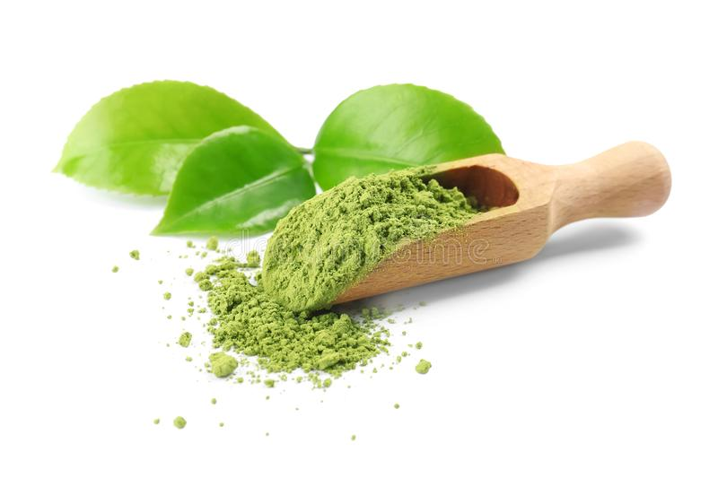 A colher com chá e verde do matcha sae no fundo branco imagem de stock royalty free