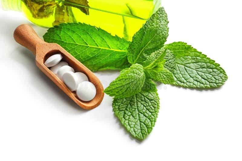 Colher com comprimidos, hortelã e garrafa do óleo essencial no fundo branco foto de stock