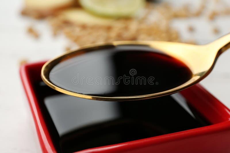 Colher com molho de soja sobre o prato imagens de stock