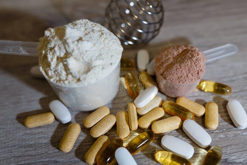 Colher com proteína do soro e colher com proteína do chocolate e ômega 3 das tabuletas e das vitaminas para esportes e a nutrição imagem de stock royalty free