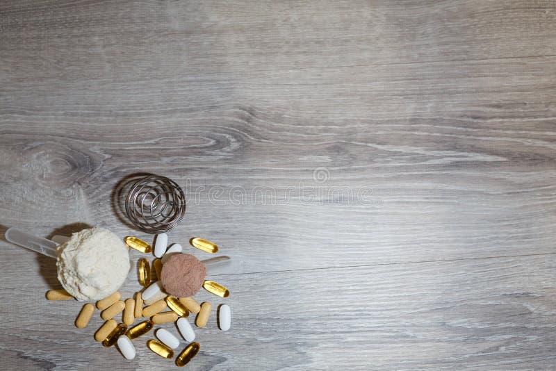 Colher com proteína do soro e colher com proteína do chocolate e ômega 3 das tabuletas e das vitaminas para esportes e a nutrição imagens de stock royalty free