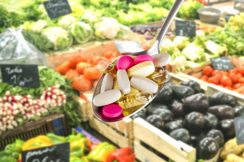 Colher com suplementos dietéticos no fundo borrado do fruto fotografia de stock