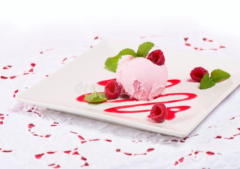 Colher cor-de-rosa do gelado com molho e bagas no pano branco fotografia de stock